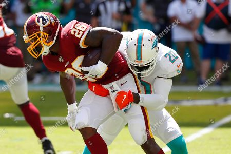 Reshad Jones, Adrian Peterson. Miami Dolphins free safety Reshad Jones (20) tackles Washington Redskins running back Adrian Peterson (26)during the first half at an NFL football game, in Miami Gardens, Fla