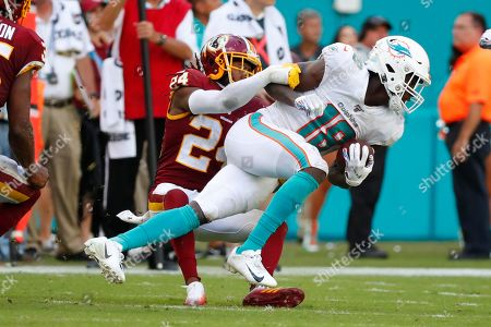 Stock Picture of Josh Norman, Preston Williams. Washington Redskins cornerback Josh Norman (24) pulls down Miami Dolphins wide receiver Preston Williams (18), during the second half at an NFL football game, in Miami Gardens, Fla