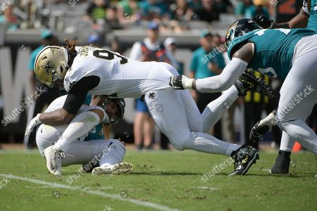 Stock Image of Jacksonville Jaguars quarterback Gardner Minshew, lower left, is sacked by New Orleans Saints defensive end Cameron Jordan, center, as Jaguars offensive tackle Jawaan Taylor, right, tries to slow Jordan down during the first half of an NFL football game, in Jacksonville, Fla