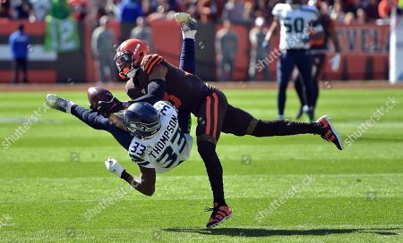 Cleveland Browns wide receiver Odell Beckham Jr. (13) catches a pass under pressure from Seattle Seahawks free safety Tedric Thompson (33) during the first half of an NFL football game, in Cleveland