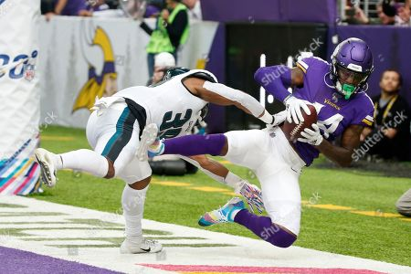 Minnesota Vikings wide receiver Stefon Diggs catches an 11-yard touchdown pass in front of Philadelphia Eagles defensive back Craig James, left, during the second half of an NFL football game, in Minneapolis