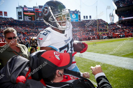 Stock Photo of Tennessee Titans cornerback Adoree' Jackson spends some time with a fan in a wheelchair before an NFL football game against the Denver Broncos, in Denver