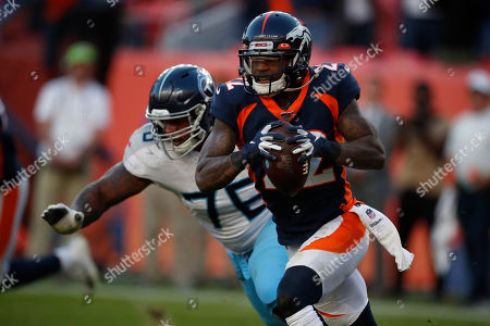 Denver Broncos defensive back Kareem Jackson (22) intercepts a pass as Tennessee Titans offensive guard Rodger Saffold chases during the second half of an NFL football game, in Denver