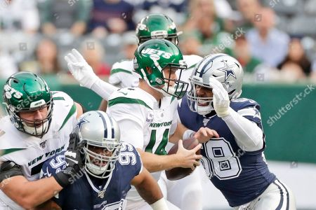 Dallas Cowboys' Robert Quinn, right, gets to New York Jets quarterback Sam Darnold during the first half of an NFL football game, in East Rutherford, N.J