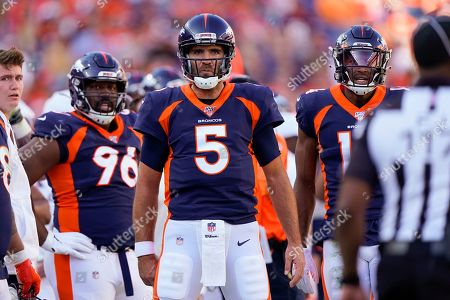 Denver Broncos quarterback Joe Flacco (5) reacts towards field judge John Jenkins, right, after a call during the first half of an NFL football game against the Tennessee Titans, in Denver