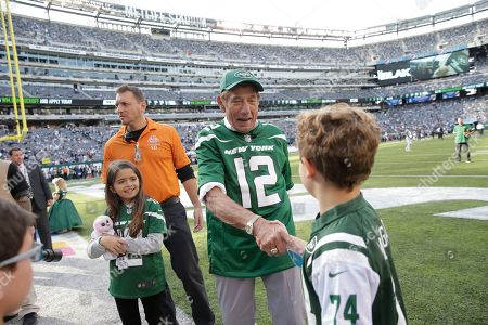 Former New York Jets quarterback Joe Namath greets people before an NFL football game between the New York Jets and the Dallas Cowboys, in East Rutherford, N.J