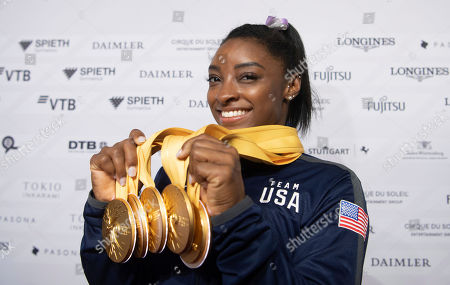Simone Biles of the United States shows her five gold medals she won at the Gymnastics World Championships in Stuttgart, Germany