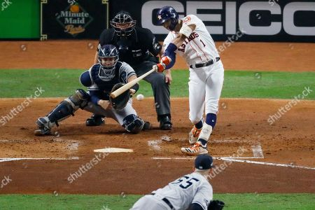 Houston Astros shortstop Carlos Correa hits a RBI-double off New York Yankees starting pitcher James Paxton during the second inning in Game 2 of baseball's American League Championship Series, in Houston