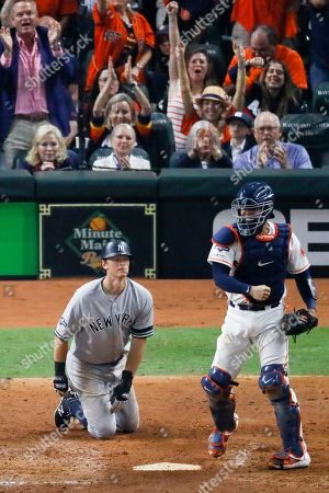 Houston Astros catcher Robinson Chirinos, right, celebrates after tagging out New York Yankees' DJ LeMahieu who tried to score on a single by Brett Gardner during the sixth inning in Game 2 of baseball's American League Championship Series, in Houston