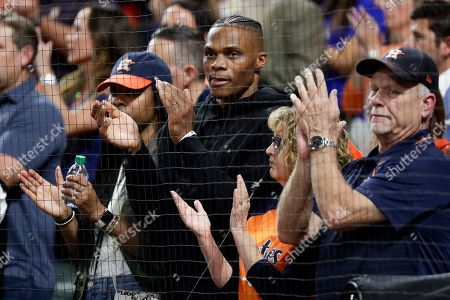 Houston Rockets's Russell Westbrook claps during the seventh inning in Game 2 of baseball's American League Championship Series between the Houston Astros and the New York Yankees, in Houston