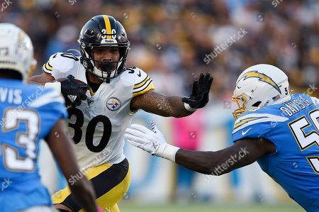 Pittsburgh Steelers running back James Conner, left, holds by Los Angeles Chargers outside linebacker Thomas Davis as he runs the ball during the first half of an NFL football game, in Carson, Calif