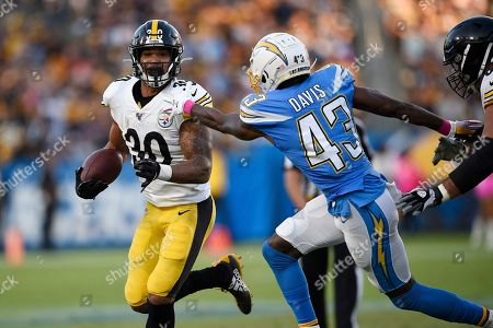Pittsburgh Steelers running back James Conner, left, runs the ball as Los Angeles Chargers cornerback Michael Davis tries to tackle him during the first half of an NFL football game, in Carson, Calif