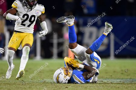 Stock Photo of Los Angeles Chargers wide receiver Jason Moore, right, rolls after making his first catch as Pittsburgh Steelers defensive back Kam Kelly watches during the second half of an NFL football game, in Carson, Calif