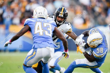 James Conner, Thomas Davis Sr. Pittsburgh Steelers running back James Conner, center, runs the ball while pressured by Thomas Davis Sr. during the first half of an NFL football game in Carson, Calif