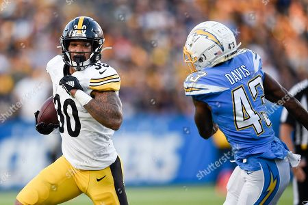 Stock Photo of James Conner, Michael Davis. Pittsburgh Steelers running back James Conner, left, runs the ball while Los Angeles Chargers cornerback Michael Davis defends during the first half of an NFL football game in Carson, Calif