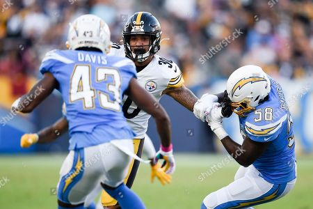 Stock Image of James Conner, Thomas Davis Sr. Pittsburgh Steelers running back James Conner, center, runs the ball while pressured by Thomas Davis Sr. during the first half of an NFL football game in Carson, Calif