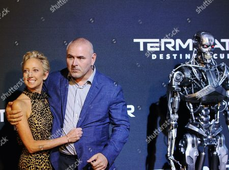 Tim Miller (R) and his wife, Jennifer Miller (L), pose next to a Terminator robot on the red carpet during the premiere of the movie 'Terminator: Dark Fate' in Mexico City, Mexico, 13 October 2019.