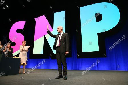 Kirsten Oswald, SNP Business Convener, and Nicola Sturgeon, First Minister of Scotland and Leader of the Scottish National Party (SNP), applaud John Swinney, Deputy First Minister and Cabinet Secretary for Education and Skills, after his address to conference.