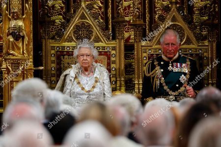 Britain's Queen Elizabeth II (L) takes her seat on the The Sovereign's Throne in the House of Lords next to Britain's Prince Charles, Prince Charles (R) before reading the Queen's Speech during the State Opening of Parliament in the Houses of Parliament. (Photo by Tolga Akmen / POOL / AFP)