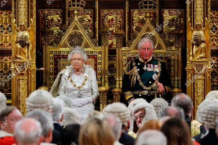Queen Elizabeth II (L) takes her seat on the The Sovereign's Throne in the House of Lords next to Prince Charles (R) before reading the Queen's Speech during the State Opening of Parliament in the Houses of Parliament in London
