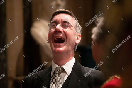 Britain's Leader of the House of Commons Jacob Rees-Mogg laughs whilst talking with someone before the arrival of Britain's Queen Elizabeth II in the Norman Porch at the Palace of Westminster and the Houses of Parliament for the State Opening of Parliament ceremony in London