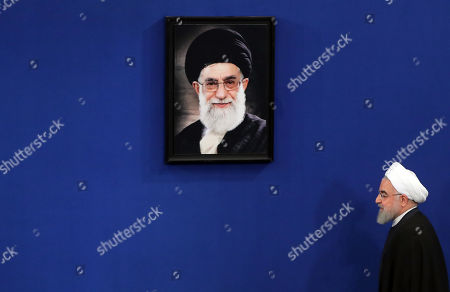 Iranian President Hassan Rouhani walks next to a picture of Iranian supreme leader Ayatollah Ali Khamenei, upon arrival for a press conference in Tehran, Iran, 14 October 2019. According to Iranian reports, Rouhani said his county overcame difficult economic situation after the foreign pressure, adding that economic indicators are getting better.