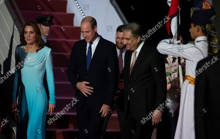 Pakistani Foreign Minister Shah Mehmood Qureshi, right, escorts Britain's Prince William and his wife Catherine Duchess of Cambridge as they arrive at the Nur Khan base in Islamabad, Pakistan. They are on a five-day visit, which authorities say will help further improve relations between the two countries