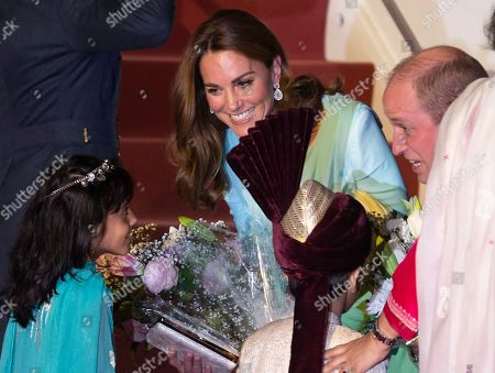Britain's Prince William and his wife Catherine Duchess of Cambridge receive flowers from a child upon their arrival at the Nur Khan base in Islamabad, Pakistan,. They are on a five-day visit, which authorities say will help further improve relations between the two countries