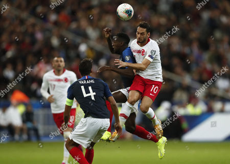Blaise Matuidi (C) and Raphael Varane (L) of France and Hakan Calhanoglu (R) of Turkey in action during the UEFA EURO 2020 qualifier soccer match between France and Turkey held at Stade de France Stadium in Paris, France, 14 October 2019.