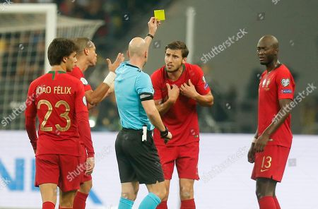 Portugal's Ruben Dias argues with referee showing him a yellow during the Euro 2020 group B qualifying soccer match between Ukraine and Portugal at the Olympiyskiy stadium in Kyiv, Ukraine