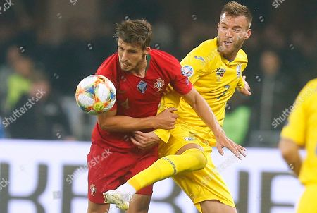 Stock Photo of Portugal's Ruben Dias, left, fights for the ball with Ukraine's Andriy Yarmolenko during the Euro 2020 group B qualifying soccer match between Ukraine and Portugal at the Olympiyskiy stadium in Kyiv, Ukraine