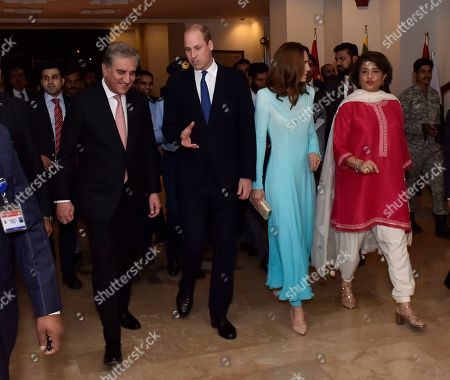 In this picture released by the Foreign Office, Pakistan's Foreign Minister Shah Mehmood Qureshi, left, escorts Britain's Prince William and his wife Catherine Duchess of Cambridge as they arrive at the Nur Khan base in Islamabad, Pakistan,. They are on a five-day visit, which authorities say will help further improve relations between the two countries
