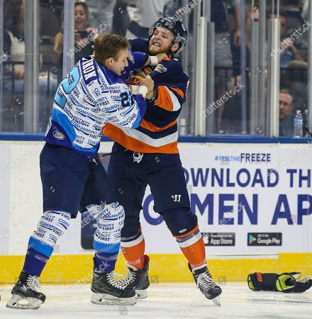 Less than a minute into the season opener Icemen forward Ian McKinnon (22), left, and Greenville Swamp Rabbits forward Travis Howe (14) drop their gloves and fight during an ECHL professional hockey game at the Veterans Memorial Arena in Jacksonville, Fla., [Gary Lloyd McCullough/CSM]