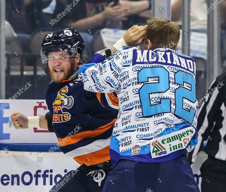 Less than a minute into the season opener Icemen forward Ian McKinnon (22), right, and Greenville Swamp Rabbits forward Travis Howe (14) drop their gloves and fight during an ECHL professional hockey game at the Veterans Memorial Arena in Jacksonville, Fla., [Gary Lloyd McCullough/CSM]
