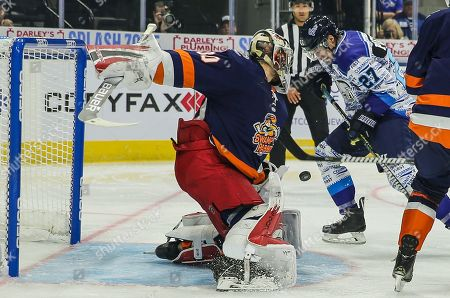 Greenville Swamp Rabbits goaltender Callum Booth (30) blocks the puck chased by Icemen forward James Phelan (27), right, during the first period of an ECHL professional hockey game at the Veterans Memorial Arena in Jacksonville, Fla., [Gary Lloyd McCullough/CSM]