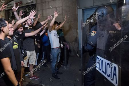 Stock Photo of Protesters shout slogans at police officers during a protest against the Spanish Supreme Court ruling in the ?proces? trial, in Barcelona, Spain, 14 October 2019. Spanish Supreme Court condemned Oriol Junqueras to 13 years in jail for sedition, Carme Forcadell to 11 and a half years for sedition; Jordi Cuixart and Jordi Sanchez were sentenced to nine and a half years for sedition; former regional Minister Jordi Turull, Raul Romeva and Dolors Bassa were sentenced to 12 years in jail for sedition and misappropriation, while Joaquin Forn and Josep Rull were sentenced to 10 and a half years for sedition. The three other defendants were absolved.