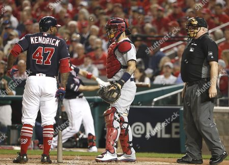 Washington Nationals second baseman Howie Kendrick (L) reacts after being called out on strikes as St. Louis Cardinals catcher Yadier Molina (C) and home plate umpire Bill Miller (R) look on during the bottom of the second inning of their MLB National League Championship Series playoff baseball game three at Nationals Park in Washington, DC, USA, 14 October 2019. The winner of the National Leauge Championship Series will play the winner of the American League Championships Series in the World Series.