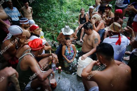 Stock Picture of Juan Carlos Paso performs a cleansing ritual on a woman in a pool of water on Sorte Mountain where followers of indigenous goddess Maria Lionza gather annually in Venezuela's Yaracuy state. Devotees say the number of followers swells as Venezuelans turn for answers to the struggle of daily life outside traditional political system, churches and hospitals