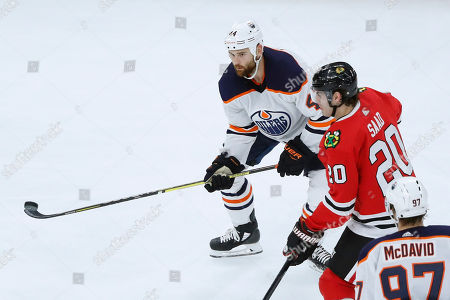 Zack Kassian, Brandon Saad, Connor McDavid. Edmonton Oilers' Zack Kassian, left, tries to advance an airborne puck as Chicago Blackhawks' Brandon Saad and Connor McDavid (97) watch during the second period of an NHL hockey game, in Chicago