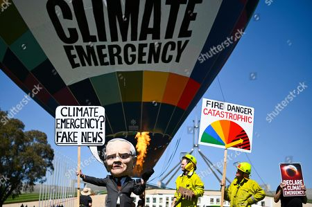 A puppet depicting Australian Prime Minster Scott Morrison is seen in front of a Climate Change Emergency hot air balloon during a Climate Change rally outside Parliament House in Canberra, Australia, 15 October 2019.