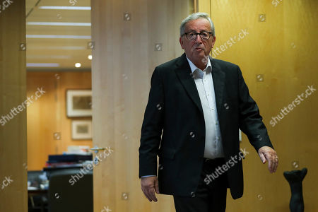 European Commission President Jean-Claude Juncker steps out his office to meet incoming European Commissioner for Economy Paolo Gentiloni before their meeting at the EU headquarters in Brussels, . The European Union said Tuesday that a Brexit divorce deal is possible this week but that the British government's proposals so far are not sufficient to seal an agreement