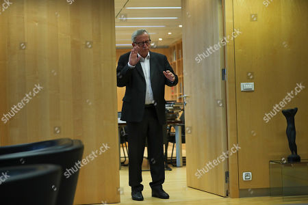 European Commission President Jean-Claude Juncker gestures to photographers before meeting incoming European Commissioner for Economy Paolo Gentiloni at the EU headquarters in Brussels, . The European Union said Tuesday that a Brexit divorce deal is possible this week but that the British government's proposals so far are not sufficient to seal an agreement