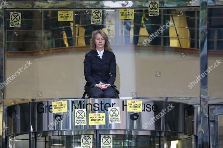 Stock Image of XR activist and co-founder Gail Bradbrook climbs on top of the entrance of the Department Transport and hammers the glass as police arrest her with a JCB.