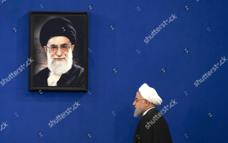 Stock Picture of Iranian President Hassan Rouhani walks past a portrait of Iran's Supreme Leader Ayatollah Ali Khamenei as he arrives a presidential building for speaking at a news conference in southern Tehran