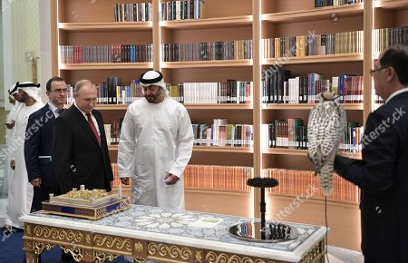 Russian President Vladimir Putin (front 2-L) looks at a model of Qasr al-Hosn Palace which was gifted to him by Abu Dhabi's Crown Prince Sheikh Mohammed bin Zayed Al Nahyan (front 3-L), while  unidentified official holds a white  a white gyrfalcon, which is a gift to Abu Dhabi's Crown Prince  from Russian President, during a ceremony of exchange of gifts in the library of the Qasr Al Watan palace in Abu Dhabi, United Arab Emirates, 15 October 2019. Russian President Vladimir Putin is on a state visit to UAE.