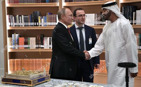 Abu Dhabi's Crown Prince Sheikh Mohammed bin Zayed Al Nahyan (R) shakes hands with Russian President Vladimir Putin (L) after they exchanged gifts their meeting in the library of the Qasr Al Watan palace in Abu Dhabi, United Arab Emirates, 15 October 2019. Abu Dhabi's Crown Prince Sheikh Mohammed bin Zayed Al Nahyan gave a model of Qasr al-Hosn Palace as a gift to Russian President, and Vladimir Putin presented him a white gyrfalcon.  Russian President Vladimir Putin is on a state visit to UAE.