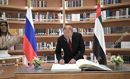 Russian President Vladimir Putin signs a guest book following gifts exchange with Abu Dhabi's Crown Prince Sheikh Mohammed bin Zayed Al Nahyan (not pictured) in the library of the Qasr Al Watan palace in Abu Dhabi, United Arab Emirates, 15 October 2019. Russian President Vladimir Putin is on a state visit to UAE.