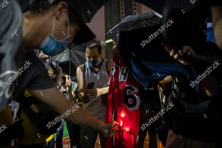 Demonstrators set a Lebron James jersey on fire during a rally at the Southorn Playground in Hong Kong, . Protesters in Hong Kong have thrown basketballs at a photo of LeBron James and chanted their anger about comments the Los Angeles Lakers star made about free speech during a rally in support of NBA commissioner Adam Silver and Houston Rockets general manager Daryl Morey, whose tweet in support of the Hong Kong protests touched off a firestorm of controversy in China