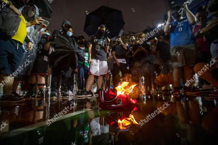 Demonstrators watch as a Lebron James jersey burns during a rally at the Southorn Playground in Hong Kong, . Protesters in Hong Kong have thrown basketballs at a photo of LeBron James and chanted their anger about comments the Los Angeles Lakers star made about free speech during a rally in support of the NBA and Houston Rockets general manager Daryl Morey, whose tweet in support of the Hong Kong protests touched off a firestorm of controversy in China