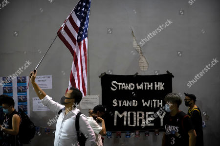 A demonstrator holds a U.S. flag during a rally at the Southorn Playground in Hong Kong, . Protesters in Hong Kong have thrown basketballs at a photo of LeBron James and chanted their anger about comments the Los Angeles Lakers star made about free speech during a rally in support of NBA commissioner Adam Silver and Houston Rockets general manager Daryl Morey, whose tweet in support of the Hong Kong protests touched off a firestorm of controversy in China